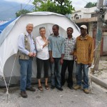 Greg, Evie, Makil and other stand in front of a tent provide by ORE.